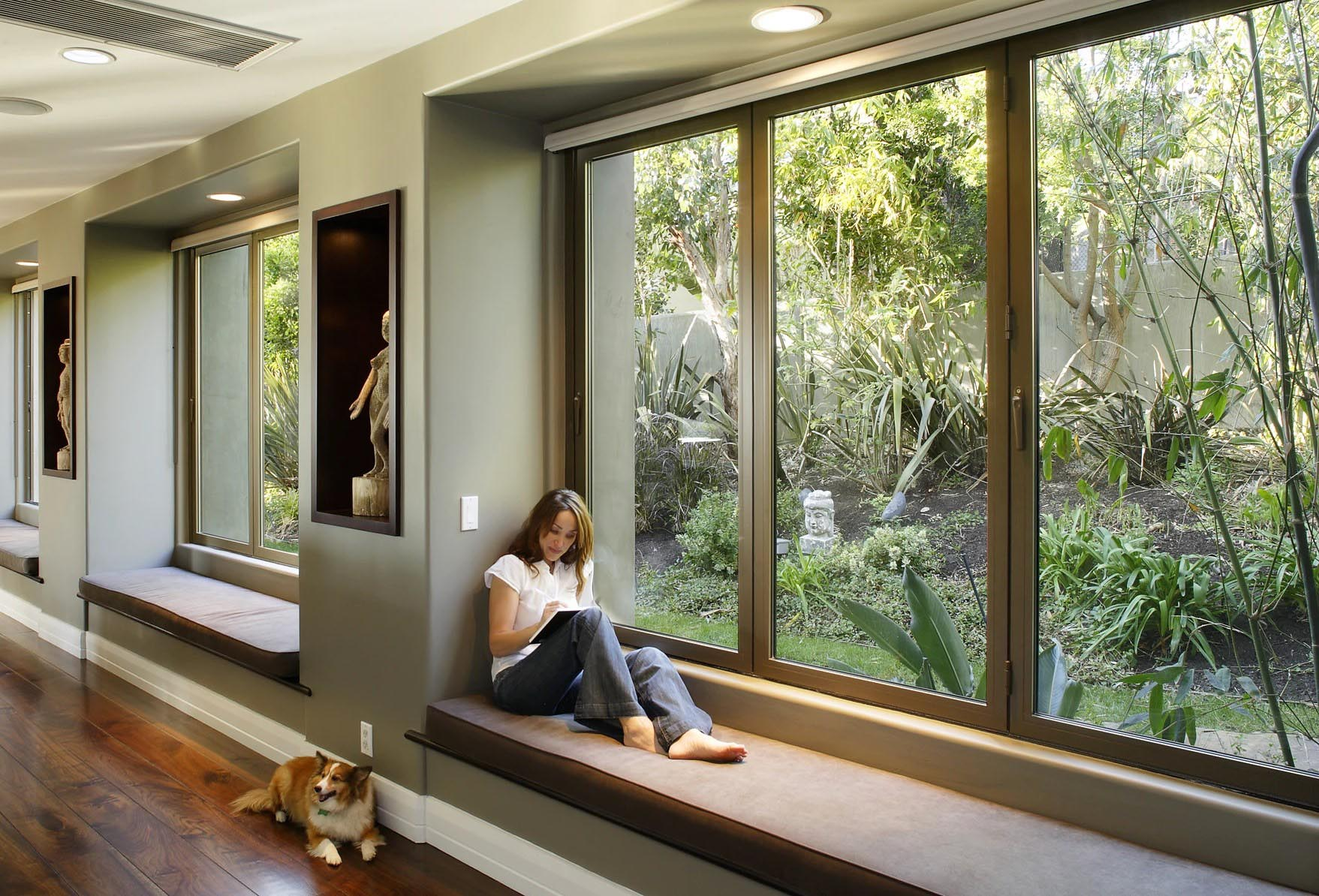 Woman exploring ideas in front of folding glass window