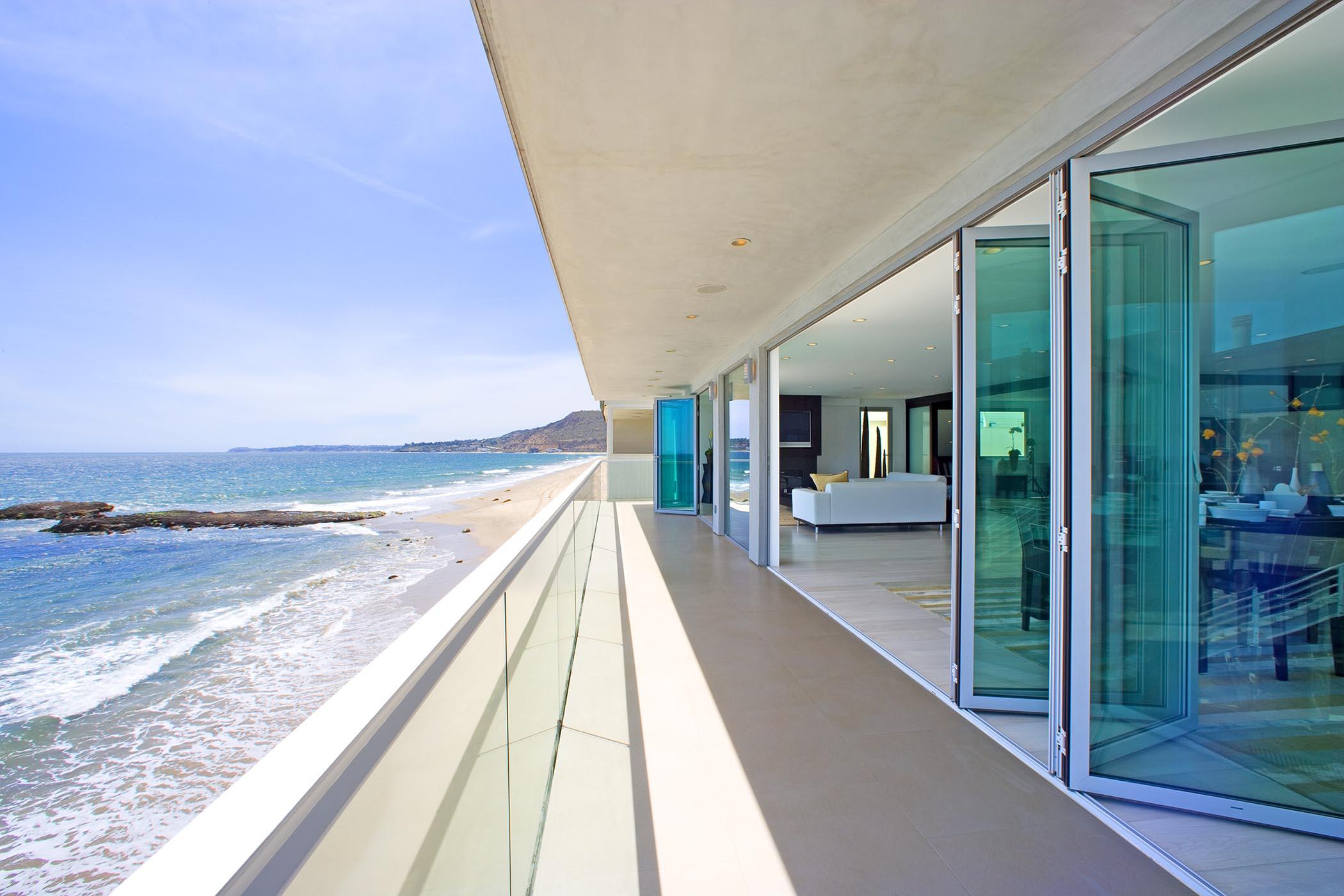 aluminum framed folding glass walls in modern oceanfront home
