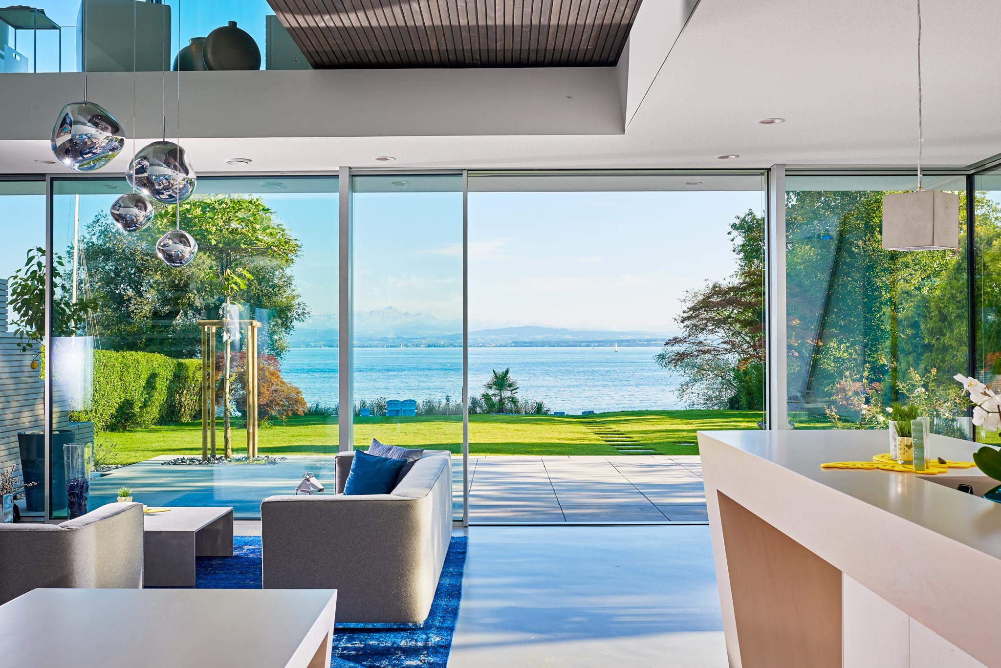 minimal sliding glass walls in serene waterfront home