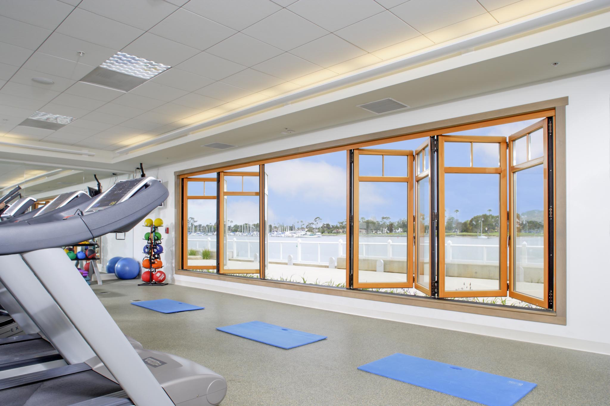 exercise room with wood framed folding glass wall open for fresh ar