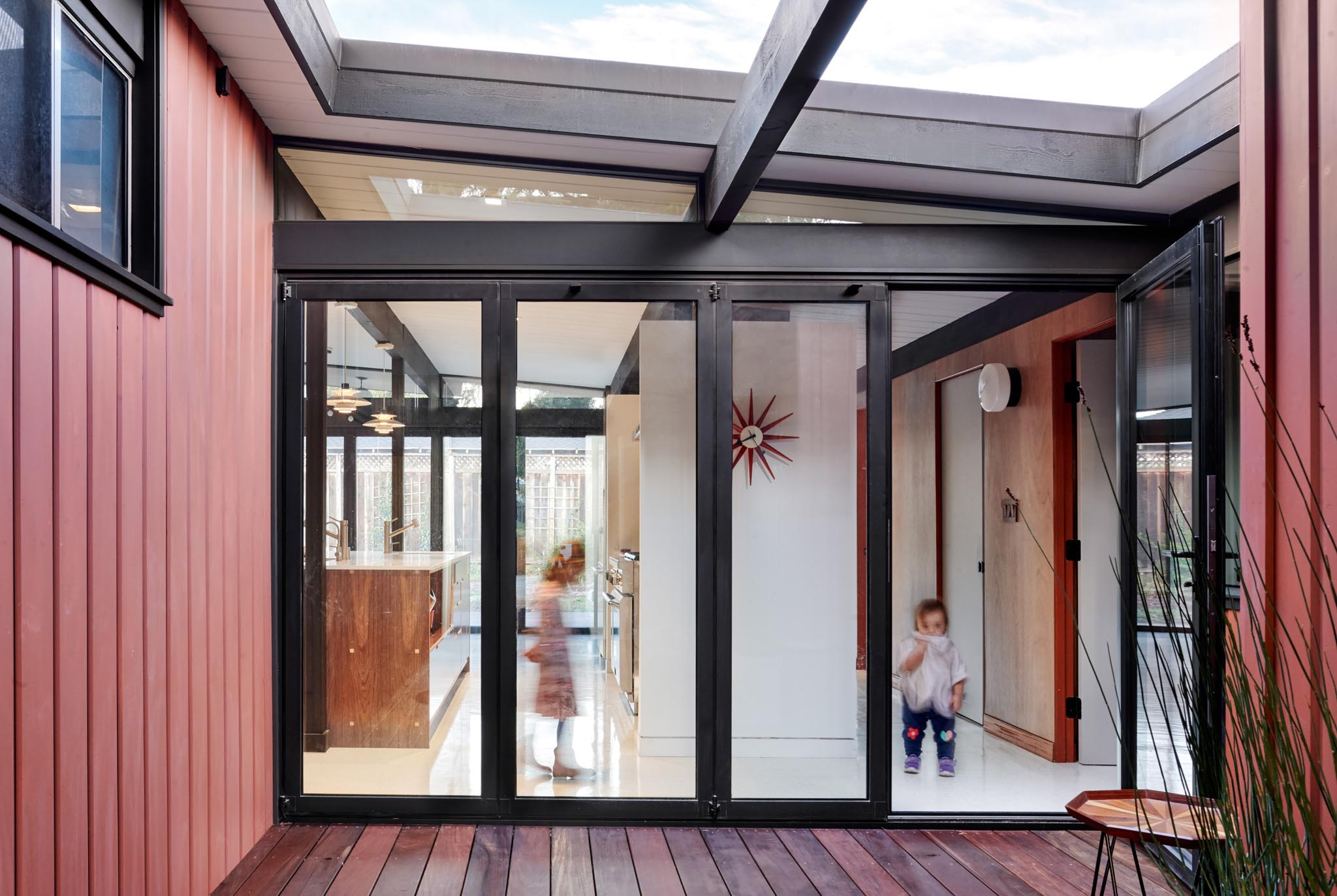 folding glass wall in Eichler remodel to connect home to courtyard