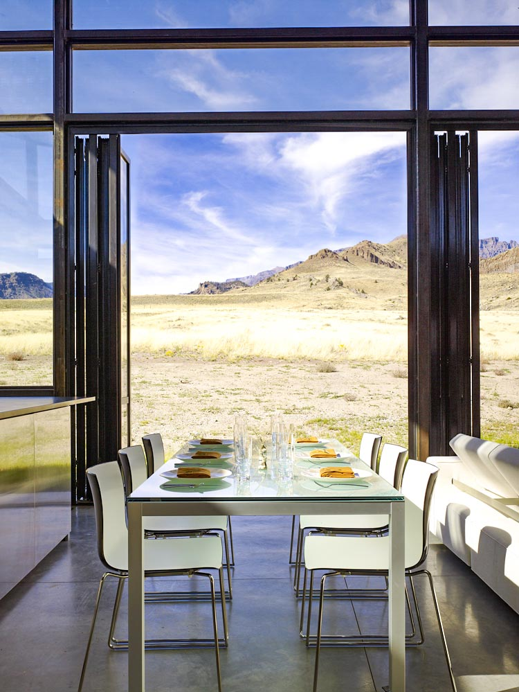 open view of nature out of folding glass wall in dining room