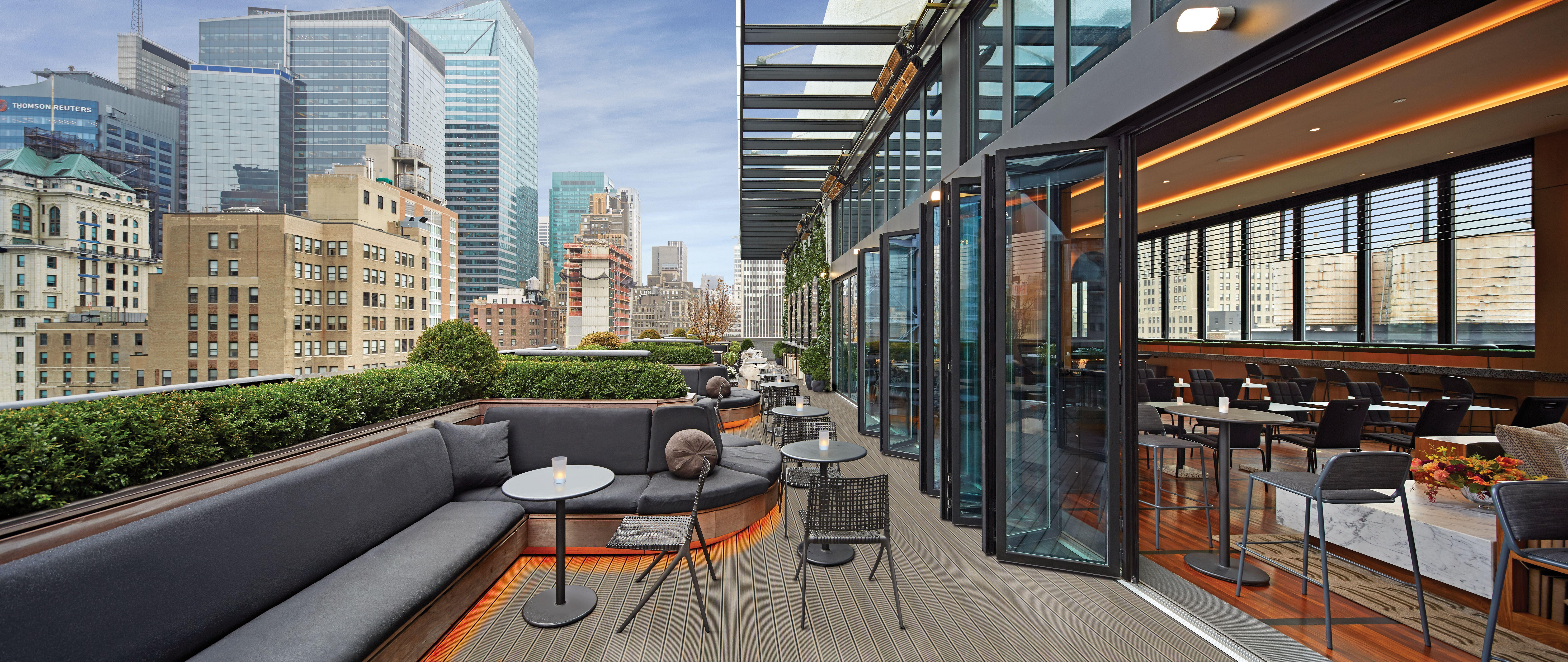 rooftop bar and restaurant in new york city with folding glass walls open to the balcony