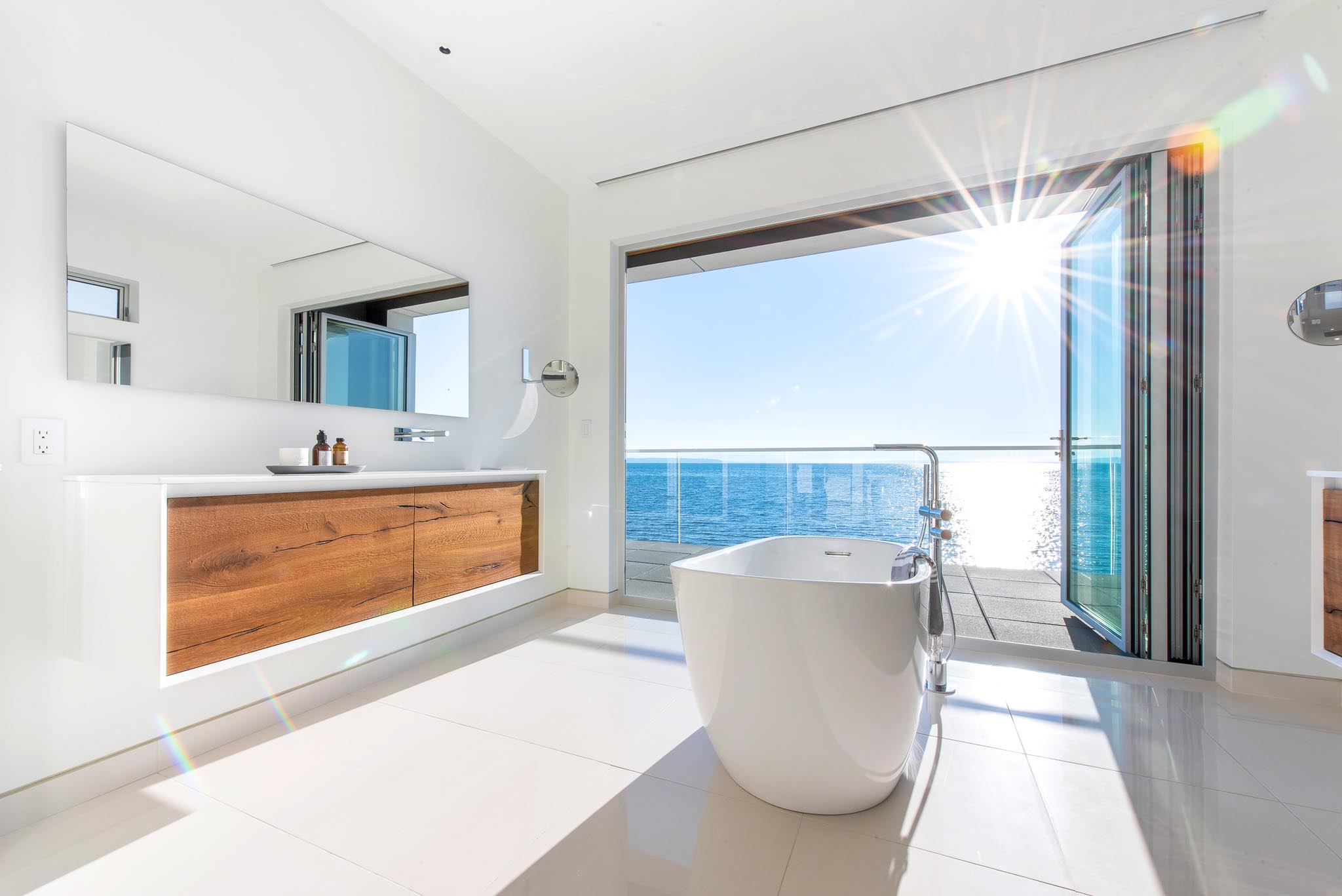 freestanding bathtub in front of open folding glass wall in oceanfront home
