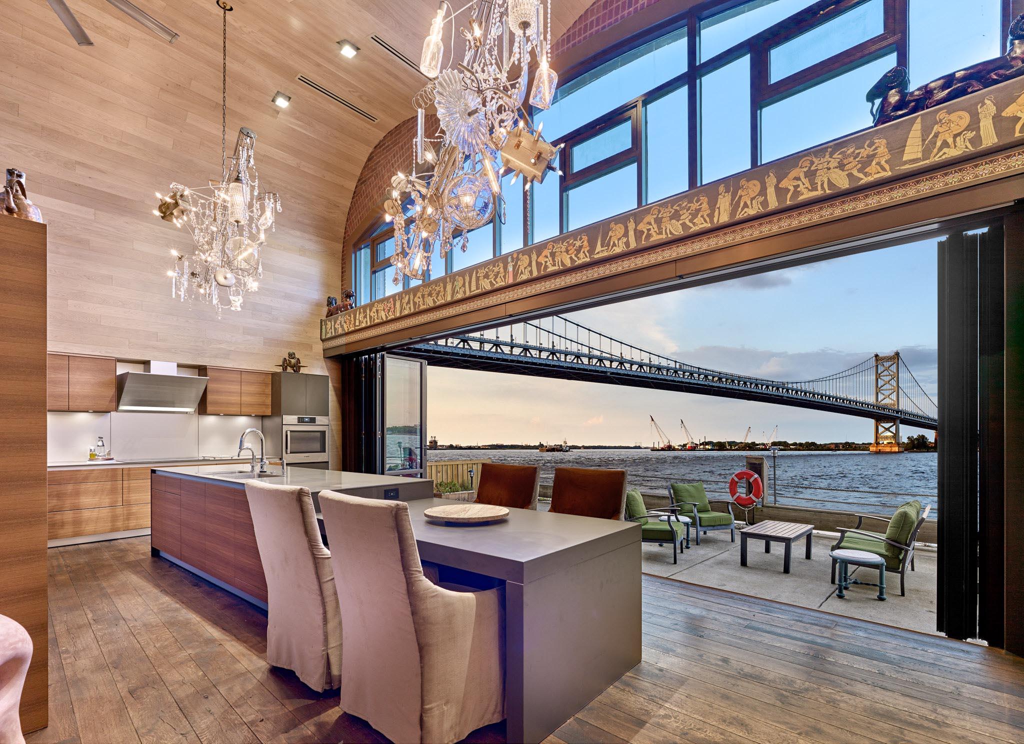 grand philadelphia kitchen with bridge view through opening glass wall