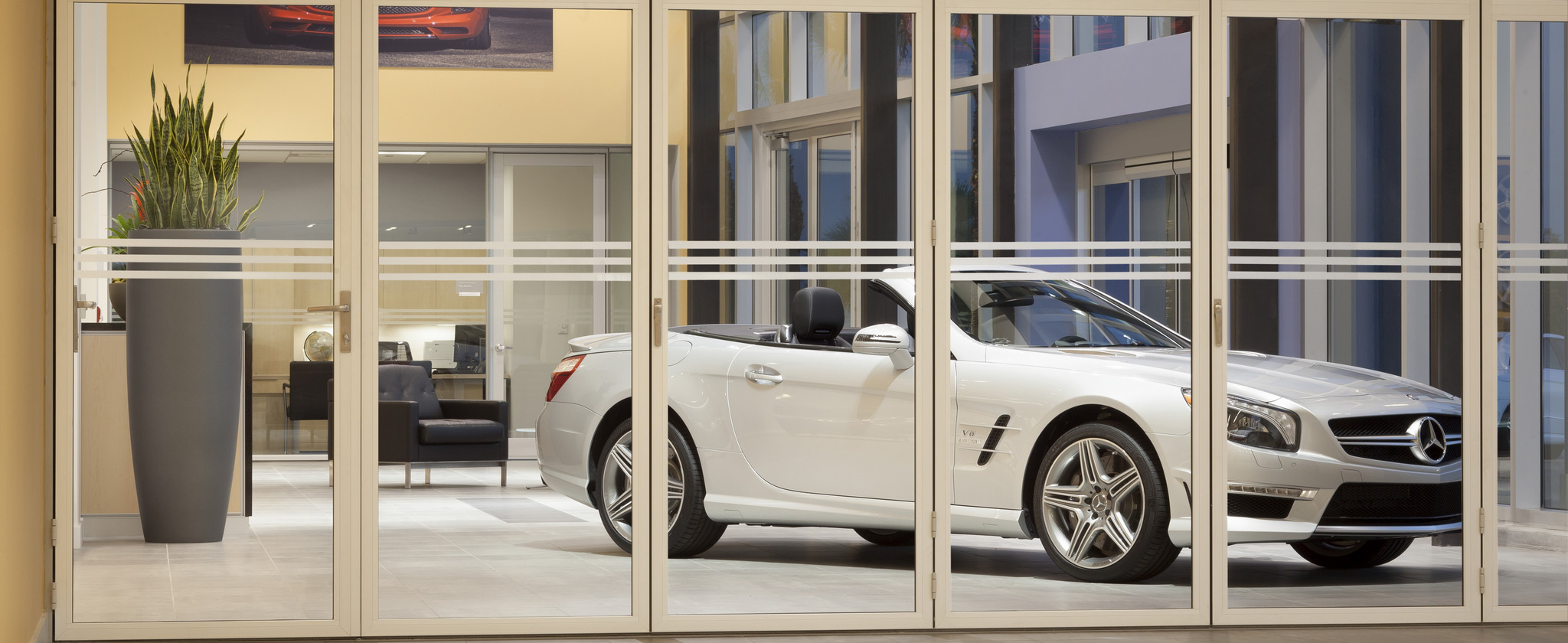 white convertible car parked in front of folding interior moveable glass doors